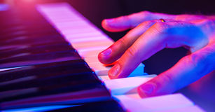 Hands of musician playing keyboard in concert with shallow depth Stock Images
