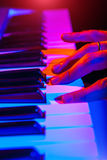 Hands of musician playing keyboard in concert with shallow depth Stock Image