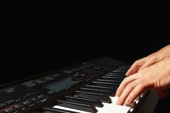Hands of musician playing the synth on black background Royalty Free Stock Image