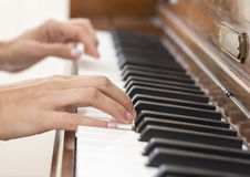 Hands of a musician playing a vintage wooden piano. Hands of a skilled musician playing a vintage brown wooden piano by touching the keyboard with talent and Royalty Free Stock Photography