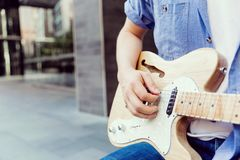 Hands of musician with guitar. Hands of musician tuning his guitar outside royalty free stock image