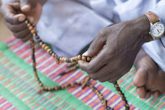 Hands of a Muslim man praying with rosary beads Royalty Free Stock Photo