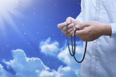 Hands of muslim person with prayer beads in hand praying. Over night scene background Royalty Free Stock Images