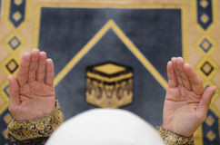 Hands of muslim woman on the carpet praying in traditional wearing clothes, Woman in Hijab, Carpet of Kaaba, royalty free stock photography