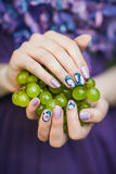 Hands with Nails Holding Grapes. Beautiful hands with wonderful nails Holding a Bunch of Green Grapes stock images