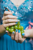 Hands with Nails Holding Grapes. Beautiful hands with wonderful nails Holding a Bunch of Green Grapes royalty free stock photo