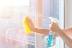 Hands with napkin cleaning window. Washing the glass on the windows with cleaning spray. Selective soft focus. Empty place for text, copy space. Window royalty free stock images