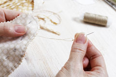 Hands needlewoman holding a needle and thread. Closeup hands needlewoman holding a needle and thread. Handicrafts and sewing. Shallow focus and blurred Royalty Free Stock Image