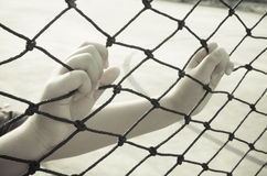 Hands with net, Hands with rope mesh fence Royalty Free Stock Photos