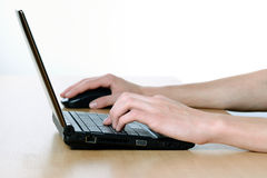 Hands and netbook on the office desk Stock Photo