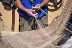 Hands and nets. Fishermen preparing fishing nets on hes boat before going at work stock photo