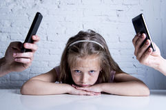 Hands of network addict parents using mobile phone neglecting little sad ignored daughter bored. Hands of internet and network addict mother and father using Stock Photo