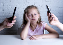 Hands of network addict parents using mobile phone neglecting little sad ignored daughter bored Royalty Free Stock Photo