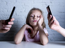 Hands of network addict parents using mobile phone neglecting little sad ignored daughter bored Royalty Free Stock Photos