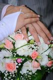 Hands of newly-married couple on a wedding bouquet Royalty Free Stock Photos