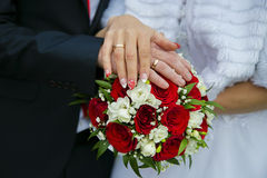 Hands of a newly-married couple on a wedding bouquet Stock Image