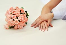 Hands of a newly wed couple. Pink roses wedding bouquet Royalty Free Stock Images