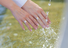 Hands of newly wedded under running water Royalty Free Stock Image