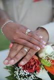 Hands of newlywed couple. Joined together showing wedding rings on top of bouquet of flowers Stock Photo