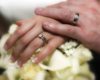 Hands of newlywed couple. Newlywed couple holding hands over bouquet of flowers with wedding rings Stock Image