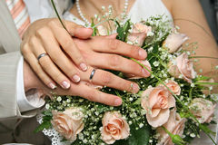Hands newlyweds. On background of the wedding bouquet Stock Photos