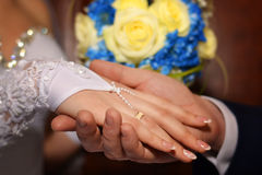 Honeymooners hands with rings on background of a bouquet of flowers. Wedding background, newlyweds hands with rings on background of a bouquet of flowers Royalty Free Stock Photos