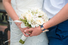 Hands newlyweds with a bouquet. A newly weding couple place their hands on a wedding bouquet Stock Photo