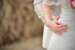 Hands newlyweds on Bridal Dress Stock Photos