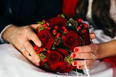 Hands of newlyweds holding a wedding bouquet Royalty Free Stock Photography