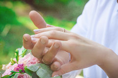 Hands of newlyweds. With rings over bouquet Stock Photos