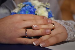 Hands of the newlyweds with rings. Wedding hands of the newlyweds with wedding rings, Bride manicure Royalty Free Stock Images