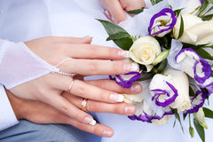 Hands of the newlyweds with wedding rings. Lie on the wedding bouquet Royalty Free Stock Photography