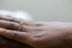 Hands of an nigerian couple. She is wearing an engagement ring Royalty Free Stock Photo