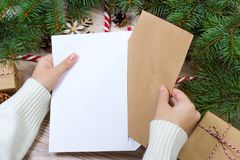 Hands with notebook and an envelop for letter. A girl is ready to send a letter with wishes to Santa Claus.  Royalty Free Stock Photography