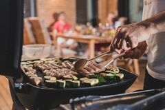 Free Hands Of A Man Seen Flipping Cevapcici Stock Images - 185509054