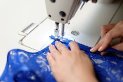 Hands Of A Woman Sewing Blue Fabric Stock Photos