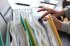 Free Hands Of Person Typing On Laptop Computer With Binders Filled With Papers In Foreground. Selective Focus Stock Image - 143530621
