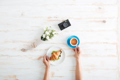 Free Hands Of Woman Drinking Coffee With Croissant On Wooden Table Stock Photos - 72919203