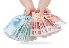 Hands offer Russian money. Two hands offer two batches of many 1000 and 5000 rouble bills (the biggest Russian bond Royalty Free Stock Photos