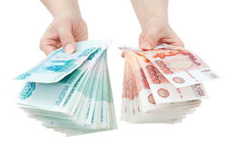 Hands offer Russian money. Two hands offer two batches of many 1000 and 5000 rouble bills (the biggest Russian bond&#x29 Stock Photo