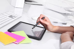 Hands on office desk using the tablet stock image