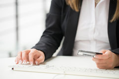 Hands of an office woman typing keyboard with credit card Royalty Free Stock Image