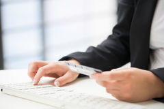 Hands of an office woman typing keyboard with credit card Royalty Free Stock Photo
