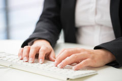 Hands of an office woman typing keyboard with credit card Royalty Free Stock Photography