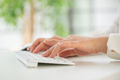 Hands of an office woman typing keyboard with credit card Stock Image