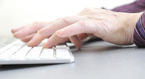 Hands of an old female typing on the keyboard. On white, close-up Royalty Free Stock Photo