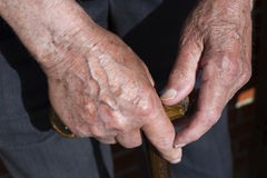 Hands. An old man with wrinkled, hands holding a stick Royalty Free Stock Images