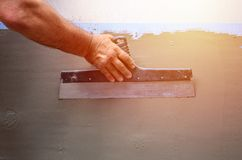 Hands of an old manual worker with wall plastering tools renovating house. Plasterer renovating outdoor walls and corners with spatula and plaster. Wall stock photos