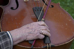 Hands Of Old Musician. Aged hands of muscican holding a bow next to a looking obsolete cello Stock Photography