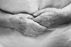 Hands of an old person. In bed stock photography